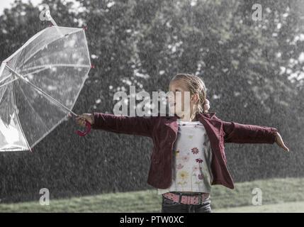Kleines Maedchen steht mit Regenschirm im Regen, lacht (model-released) - Stock Photo