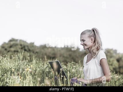 Junge Frau sitzt in Wiese mit Laptop (model-released) - Stock Photo