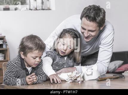 Kinder und Vater zaehlen Geld aus zerschlagenem Sparschwein (model-released) - Stock Photo