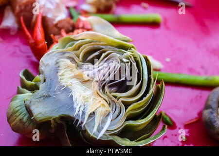 Boiled artichoke cut in half lying on pink tablecloth with mushroom and asparagus at crawfish boil - selective focus - Stock Photo