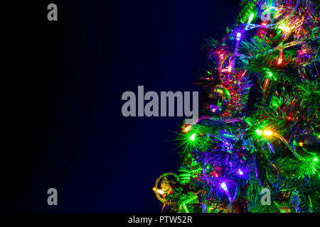 Colored decoration of Christmas tree on dark background. Part of X-mas tree with lighting bulb and decoration at night. - Stock Photo