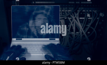 Hacker with laptop on a dark background of structured cabling. Close-up of male hands in black gloves on keyboard, motion blur. Spy's head in hood. - Stock Photo
