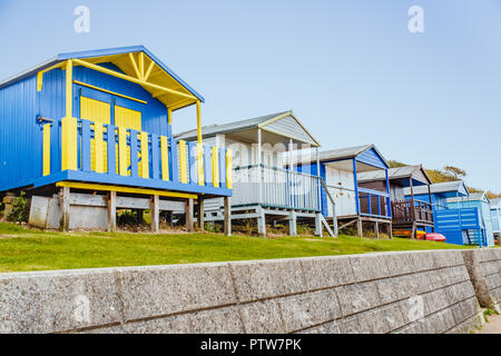 Quaint wooden beach huts in a row along a grass verge above a stone wall in Tankerton, Whitstable, Kent, UK - Stock Photo