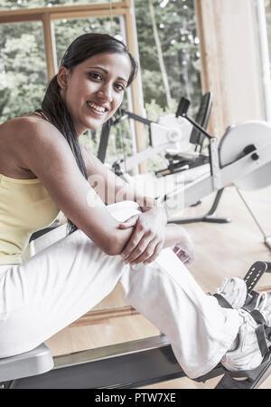 Junge Frau sitzt auf Fitnessgeraet (model-released) - Stock Photo