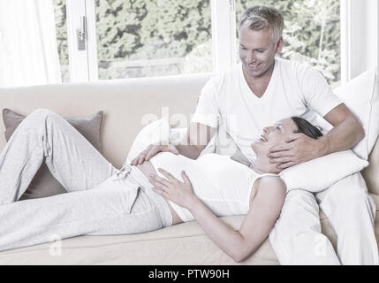 Mann streichelt auf Sofa schwangere Frau (model-released) - Stock Photo