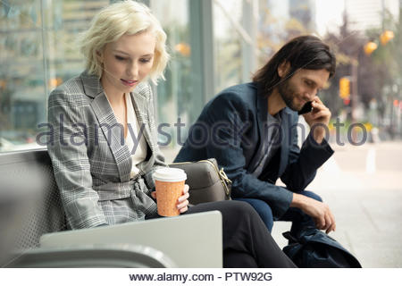 Businessman and businesswoman with coffee working at laptop and talking on smart phone on urban bench - Stock Photo