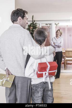 Vater und Sohn ueberraschen Mutter mit Weihnachtspaeckchen (model-released) - Stock Photo