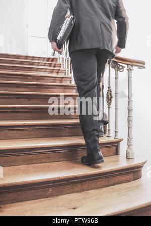 Mann mit Aktentasche geht Holztreppe hinauf (model-released) - Stock Photo