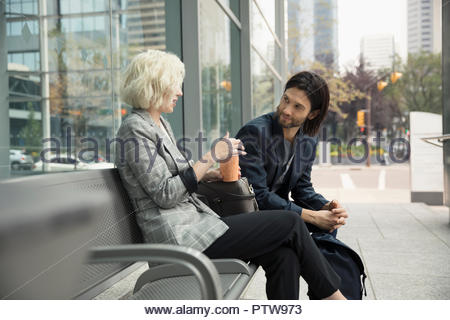 Businessman and businesswoman drinking coffee and talking on urban bench - Stock Photo
