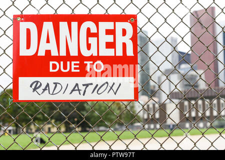 Sign danger due to radiation attached on the fence in the front of the town - Stock Photo