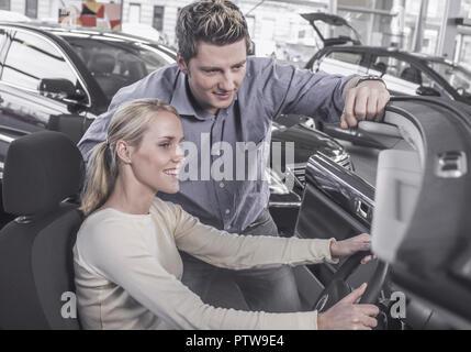 Autohaus, junges Paar sieht sich Cabrio an, sie sitzt im Auto (model-released) - Stock Photo