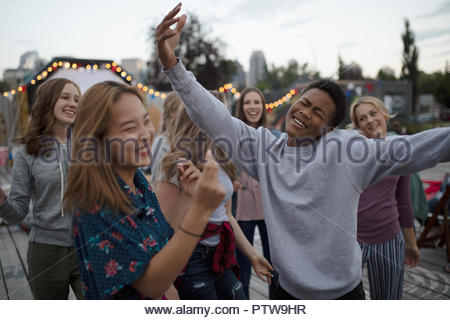 Playful teenagers dancing at movie in the park - Stock Photo