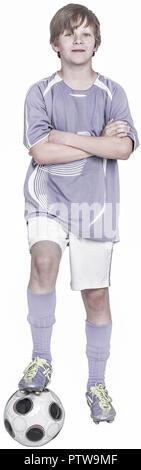 Junge steht mit einem Bein auf Fussball, verschraenkte Arme (model-released)
