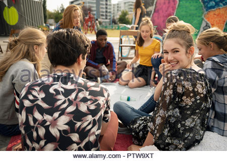 Portrait smiling teenage girl hanging out with friends, playing spin the bottle - Stock Photo