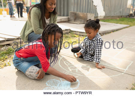 Mother and daughters drawing with sidewalk chalk - Stock Photo