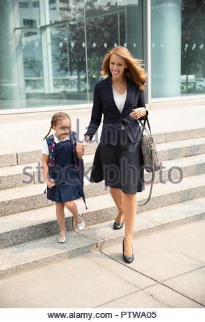 Businesswoman mother and schoolgirl daughter walking on urban sidewalk - Stock Photo