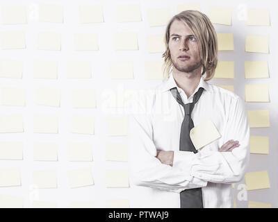 Junger Mann steht in Hemd und Krawatte vor Postit-Wand, verschraenkte Arme (model-released)