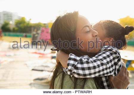 Affectionate mother and daughter hugging - Stock Photo