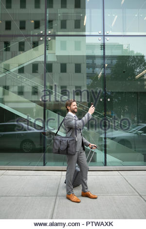 Businessman with suitcase using camera phone on urban sidewalk - Stock Photo