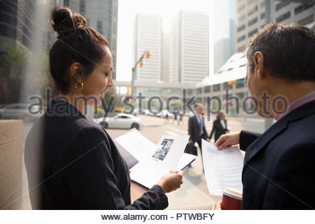 Businessman and businesswoman working, reviewing paperwork on city sidewalk - Stock Photo