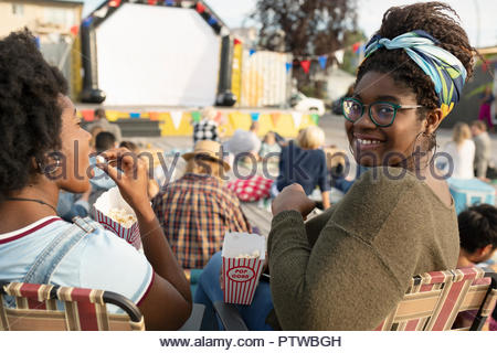 Portrait smiling young woman eating popcorn, enjoying movie in the park - Stock Photo