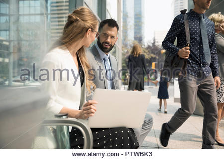 Businessman and businesswoman working at laptop on urban bench - Stock Photo