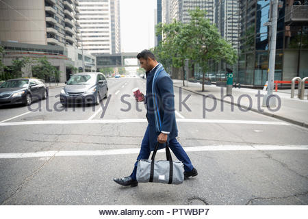 Businessman with coffee and gym bag crossing city street - Stock Photo
