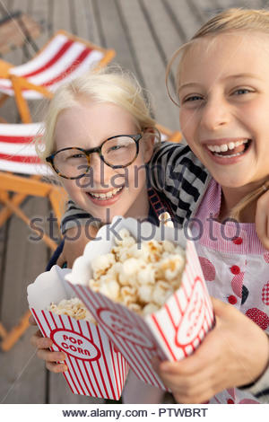 Portrait smiling, enthusiastic sisters with popcorn - Stock Photo
