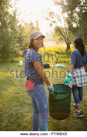 Portrait smiling teenage girl volunteering, cleaning up garbage in park with mother - Stock Photo