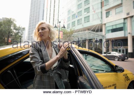 Young businesswoman getting out of taxi on urban street - Stock Photo