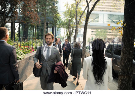 Business people walking on city sidewalk - Stock Photo