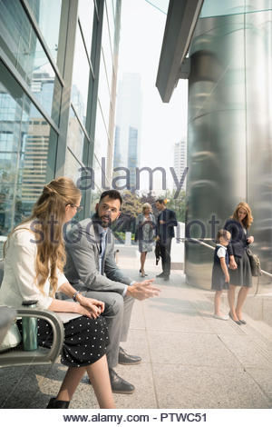 Business people talking on urban bench - Stock Photo