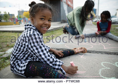 Portrait smiling, cute girl drawing with sidewalk chalk - Stock Photo