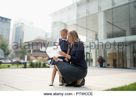 Businesswoman mother and schoolgirl daughter looking at map on urban sidewalk - Stock Photo