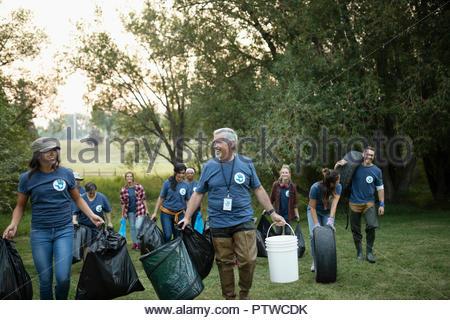 People volunteering, cleaning up garbage in park - Stock Photo
