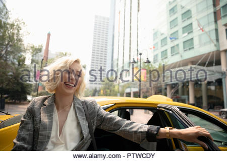 Laughing young businesswoman getting out of taxi on urban street - Stock Photo