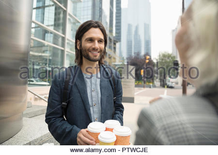 Smiling businessman with coffee talking with colleague on city street - Stock Photo