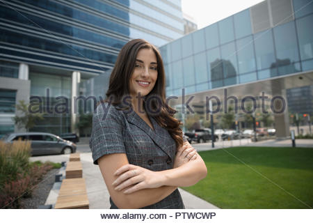 Portrait confident, smiling businesswoman in urban plaza - Stock Photo
