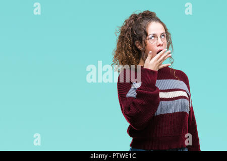 Beautiful brunette curly hair young girl wearing glasses over isolated background bored yawning tired covering mouth with hand. Restless and sleepines - Stock Photo