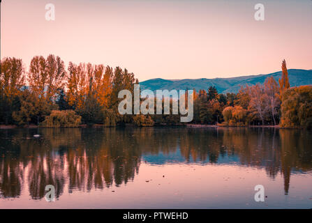 Teal and orange mood of autumn colors and reflection on the Puigcerda's pond water - Stock Photo
