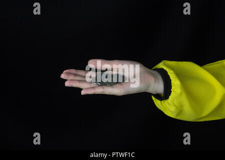 Girl holding a coin on his outstretched hand, in the palm of his hand, close-up, black background, studio - Stock Photo