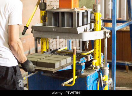 The worker makes a sidewalk tile behind the machine, a close-up, paving slab, manufacture of paving slabs - Stock Photo