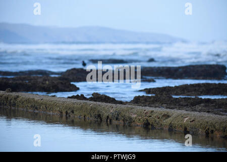 Calm Water In A Manmade Tide Pool With Rocks And Waves Defocused Background - Stock Photo