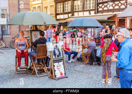 Strasbourg, France - September 09, 2018: street painter and other unidentified people on the forecourt of the Strasbourg Cathedral. Strasbourg is the  - Stock Photo