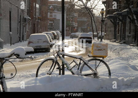 Sunny winter morning in Montreal, Canada : A bike attached to a sign pole on the sidewalk, next to a small, snow-covered street with parked cars. - Stock Photo