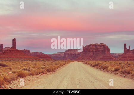Valley of the Gods rock formation with Monument Valley at sunrise - Stock Photo