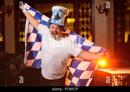 cheerful fat man with a big belly with an oktoberfest flag and a Bavarian hat on a pub background - Stock Photo