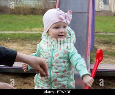 Little girl playing in a sandbox with a red scapula - Stock Photo