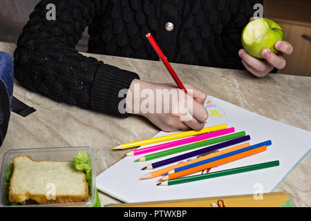 girl doing homework and eating apple, close up - Stock Photo