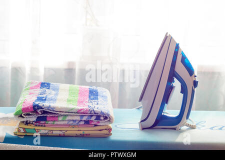 A pile of clothes and an iron on the ironing board - Stock Photo